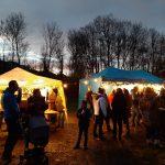 Viele Leute stehen im Freien aus dem weihnachtlich geschmücktem Platz