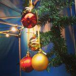 Weihnachtliches Motiv: Goldene und rote Kugeln hängen an einem Tannenast.